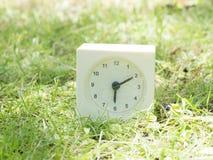 Άσπρο απλό ρολόι στο ναυπηγείο χορτοταπήτων, 6:10 έξι δέκα Στοκ Εικόνες
