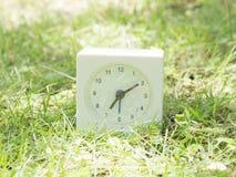 Άσπρο απλό ρολόι στο ναυπηγείο χορτοταπήτων, 7:10 επτά δέκα Στοκ εικόνες με δικαίωμα ελεύθερης χρήσης