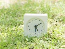 Άσπρο απλό ρολόι στο ναυπηγείο χορτοταπήτων, 5:10 πέντε δέκα Στοκ Εικόνες