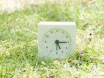 Άσπρο απλό ρολόι στο ναυπηγείο χορτοταπήτων, 5:15 πέντε δεκαπέντε Στοκ φωτογραφία με δικαίωμα ελεύθερης χρήσης