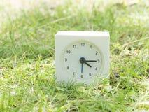 Άσπρο απλό ρολόι στο ναυπηγείο χορτοταπήτων, 4:15 τέσσερα δεκαπέντε Στοκ Φωτογραφίες