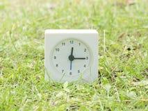Άσπρο απλό ρολόι στο ναυπηγείο χορτοταπήτων, 12:15 δώδεκα δεκαπέντε Στοκ φωτογραφία με δικαίωμα ελεύθερης χρήσης