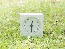 Άσπρο απλό ρολόι στο ναυπηγείο χορτοταπήτων, 12:30 δώδεκα τριάντα μισά Στοκ Φωτογραφίες