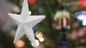 Άσπρο αστέρι σε ένα χριστουγεννιάτικο δέντρο με το θολωμένο υπόβαθρο Χριστουγεννιάτικο δέντρο με θολωμένα τα Defocused φω'τα Boke φιλμ μικρού μήκους