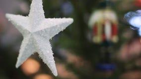 Άσπρο αστέρι σε ένα χριστουγεννιάτικο δέντρο με το θολωμένο υπόβαθρο Χριστουγεννιάτικο δέντρο με θολωμένα τα Defocused φω'τα Boke απόθεμα βίντεο