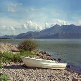 Άσπρο αλιευτικό σκάφος στην ακτή της λίμνης Skadar Μαυροβούνιο Φωτογραφία ταινιών 25 Αυγούστου 2016 Στοκ Φωτογραφίες