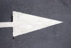Άσπρο βέλος στο μαύρο tarmac στοκ εικόνα με δικαίωμα ελεύθερης χρήσης
