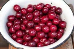 άσπρο βαθύ πιάτο με τα κόκκινα μούρα κερασιών στοκ εικόνα