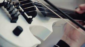 Άσπρο βιολί στα χέρια στη συναυλία φιλμ μικρού μήκους