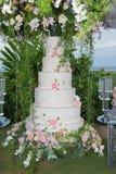 Άσπρο γαμήλιο κέικ με τα λουλούδια Γάμος παραλιών στοκ φωτογραφία με δικαίωμα ελεύθερης χρήσης