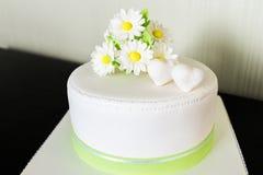 Άσπρο γαμήλιο κέικ από τη μαστίχα με το chamomile ντεκόρ Στοκ Φωτογραφία