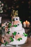 Άσπρο γαμήλιο κέικ με τη μαστίχα, που διακοσμείται με τα τριαντάφυλλα και τις επιστολές Στοκ Εικόνα