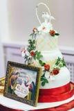 Άσπρο γαμήλιο κέικ που διακοσμούνται με τις κόκκινες κορδέλλες και το εικονίδιο στο θόριο Στοκ εικόνες με δικαίωμα ελεύθερης χρήσης