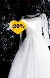 Άσπρο γαμήλιο φόρεμα με το σημάδι πώλησης μιας έκπτωσης στο παράθυρο Στοκ φωτογραφία με δικαίωμα ελεύθερης χρήσης