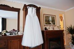 Άσπρο γαμήλιο φόρεμα στις κρεμάστρες για τη νύφη στο δωμάτιο Στοκ Φωτογραφίες