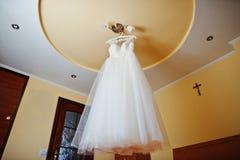 Άσπρο γαμήλιο φόρεμα στις κρεμάστρες στον πολυέλαιο στο ανώτατο όριο Στοκ Φωτογραφίες