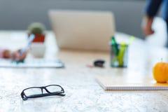 Άσπρο γραφείο γραφείων με τα γυαλιά στη μαύρη κινηματογράφηση σε πρώτο πλάνο πλαισίων Στοκ εικόνα με δικαίωμα ελεύθερης χρήσης