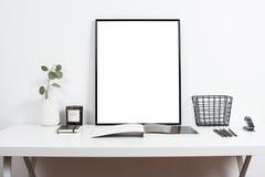 Άσπρο επιτραπέζιο διάστημα εργασίας γραφείων εσωτερικό, μοντέρνο με την αφίσα artw στοκ εικόνες