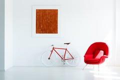 Άσπρο εσωτερικό καθιστικών με μια κόκκινα πολυθρόνα, ένα ποδήλατο και ένα paintin Στοκ εικόνες με δικαίωμα ελεύθερης χρήσης