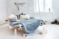 Άσπρο εσωτερικό σοφιτών στο κλασικό Σκανδιναβικό ύφος Κρεμώντας κρεβάτι που αναστέλλεται από το ανώτατο όριο Άνετο μεγάλο διπλωμέ Στοκ φωτογραφίες με δικαίωμα ελεύθερης χρήσης
