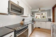 Άσπρο εσωτερικό δωματίων κουζινών με τις γκρίζες λεπτομέρειες Στοκ φωτογραφία με δικαίωμα ελεύθερης χρήσης