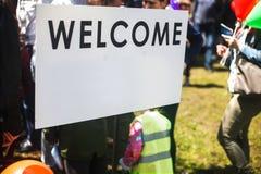 Άσπρο ευπρόσδεκτο σημάδι στην οδό Θολωμένοι άνθρωποι που επισκέπτονται ένα γεγονός στην πόλη στοκ εικόνα με δικαίωμα ελεύθερης χρήσης