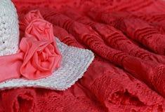 Άσπρο θερινό καπέλο με τα ρόδινα λουλούδια σε μια κόκκινη δαντέλλα Στοκ εικόνα με δικαίωμα ελεύθερης χρήσης