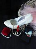Άσπρο θηλυκό παπούτσι με τα υψηλά τακούνια, το κόκκινα κραγιόν και το smartphone με τη φωτογραφία στην οθόνη Στοκ Εικόνες