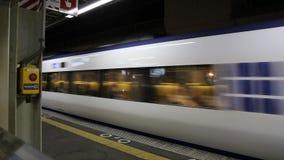Άσπρο ιαπωνικό τραίνο που αφήνει το σταθμό τη νύχτα απόθεμα βίντεο