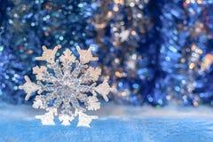 Άσπρο διαφανές snowflake παιχνιδιών Χριστουγέννων στο λαμπιρίζοντας φωτεινό BL στοκ φωτογραφία