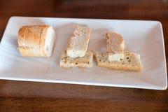 Άσπρο ιταλικό εύγευστο χειροτεχνικό ψωμί με σε ένα άσπρο πιάτο στοκ εικόνα