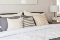 άσπρο κάλυμμα με το σύνολο μαξιλαριών στο κρεβάτι Στοκ Εικόνα