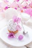 Άσπρο κέικ με την πρωτεΐνη κρέμας με το ντεκόρ των ρόδινων λουλουδιών σε έναν ξύλινο πίνακα Στοκ εικόνα με δικαίωμα ελεύθερης χρήσης