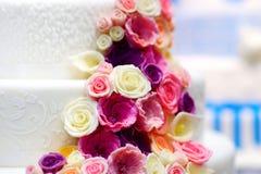 Άσπρο κέικ που διακοσμείται γαμήλιο με τα λουλούδια ζάχαρης Στοκ Φωτογραφία