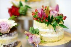 Άσπρο κέικ που διακοσμείται γαμήλιο με τα λουλούδια Στοκ εικόνα με δικαίωμα ελεύθερης χρήσης