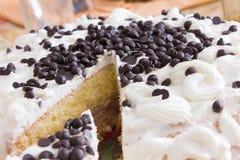 Άσπρο κέικ που διακοσμείται με την κρέμα και τη μαύρη φέτα σοκολάτας Στοκ Φωτογραφία