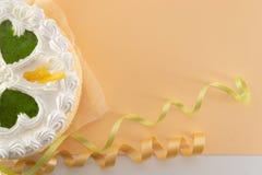Άσπρο κέικ σε ένα χρωματισμένο υπόβαθρο με τις κορδέλλες πυροβοληθείσες άνωθεν στοκ εικόνα