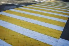 Άσπρο κίτρινο ζέβες πέρασμα διαβάσεων πεζών Για τους πεζούς πέρασμα με τη σκιά Στοκ Φωτογραφία