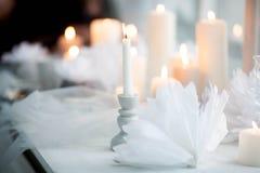 Άσπρο καίγοντας κερί σε ένα κηροπήγιο σε ένα υπόβαθρο των κεριών Στοκ εικόνα με δικαίωμα ελεύθερης χρήσης
