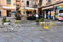 Άσπρο και κίτρινο ποδήλατο με τα λουλούδια σε Tropea στοκ εικόνες