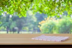 Άσπρο και κόκκινο ύφασμα ταρτάν στον ξύλινο πίνακα πέρα από τον κήπο θαμπάδων backgr Στοκ φωτογραφία με δικαίωμα ελεύθερης χρήσης