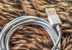 Άσπρο καλώδιο τηλεφωνικών υπολογιστών USB που κουλουριάζεται και που βάζει στο υπόβαθρο γουνών στοκ εικόνα
