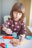 Άσπρο καυκάσιο plasticine παιχνιδιού κοριτσιών preschooler playdough στο εσωτερικό στο σπίτι Στοκ Φωτογραφία