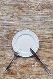 Άσπρο κενό πιάτο στον ξύλινο πίνακα Στοκ εικόνα με δικαίωμα ελεύθερης χρήσης