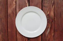 Άσπρο κενό πιάτο στον ξύλινο πίνακα Στοκ φωτογραφία με δικαίωμα ελεύθερης χρήσης