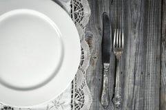 Άσπρο κενό πιάτο στο τραπεζομάντιλο με τη δαντέλλα, κοντά στο μαχαίρι και τα FO Στοκ Εικόνα