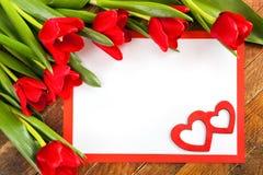 Άσπρο κενό φύλλο, κόκκινο πλαίσιο, κόκκινες τουλίπες και δύο κόκκινες καρδιές επάνω Στοκ Εικόνες