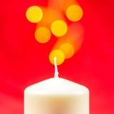 Άσπρο κερί κεριών Χριστουγέννων στο κόκκινο υπόβαθρο Στοκ Εικόνες