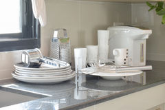 Άσπρο κεραμικό σύνολο και ανοξείδωτα εργαλεία κουζινών στο μετρητή στοκ φωτογραφίες