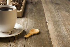 Άσπρο κεραμικό φλυτζάνι καφέ στην αγροτική επιτραπέζια ρύθμιση στοκ φωτογραφία